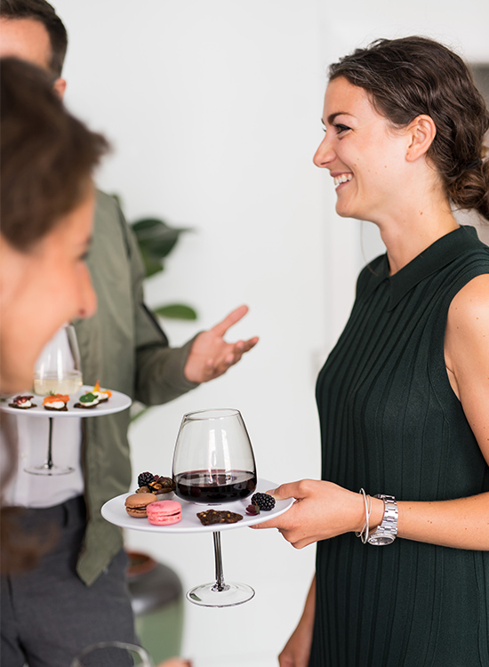 Girl networking and having fun while holding a plate and a glass using just one hand